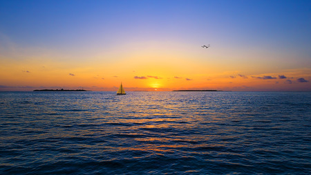 disappears: Sunset in the Maldives. The sun disappears behind the sea horizon. Stock Photo