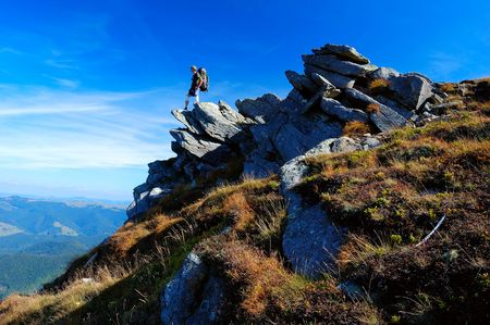 The guy costs on a rock in mountains. The picture is made in Ukraine, mountains Carpathians.
