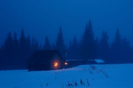 High-mountainous small house in the Ukrainian Carpathians. Winter evening, on a cross with Jesus burns a candle Imagens