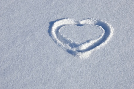 Background with a heart drawn on white snow Archivio Fotografico