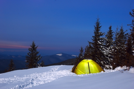 Evening in mountains in the winter with tourist tent