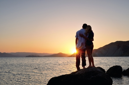 Man and woman standing arm in arm on a rock by the sea and watching the sunset
