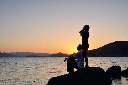 Young couple admiring the sunset on the beach