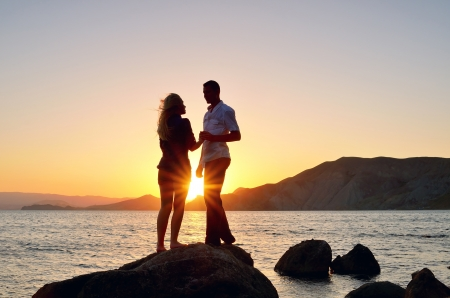 Young couple talking to a rock by the sea at the setting sun Фото со стока
