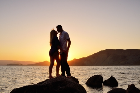 Young couple kissing on the beach at sunset photo