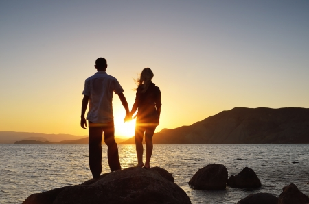 Girl and boy holding hands and watching the sun by the sea 스톡 콘텐츠