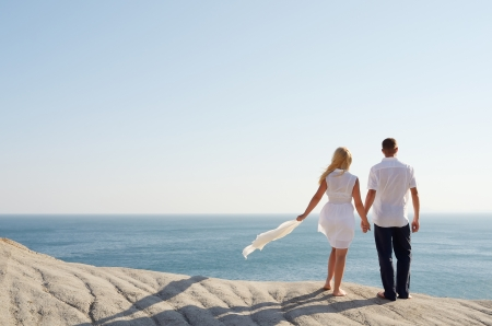Loving couple looking at the sea holding hands photo