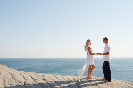 Young couple relaxing near the sea while standing on a rock photo