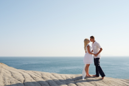 Couple kissing by the sea while standing on a rock photo