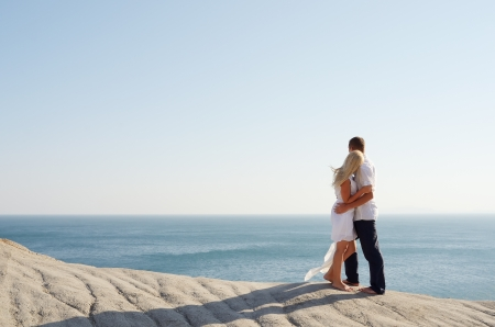 Young girl and boy standing arm in arm near the sea photo
