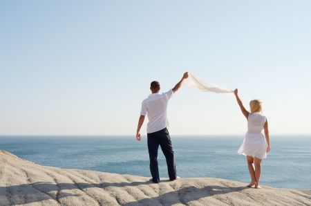 Couple holding a white handkerchief, and looks at the sea photo