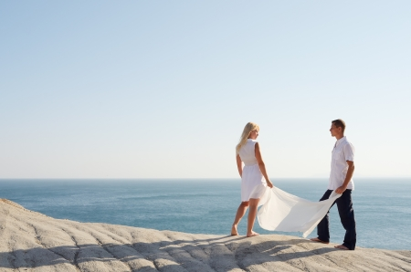 Boy and girl holding a white shawl standing on a rock and look at each other photo