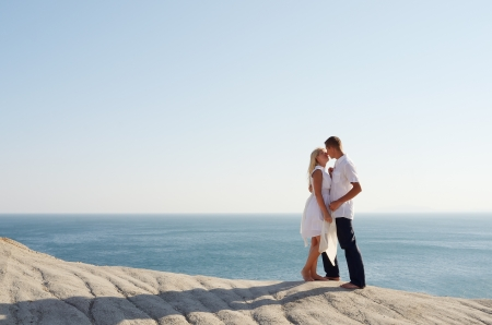 Kiss of a young couple dressed in white near the sea photo