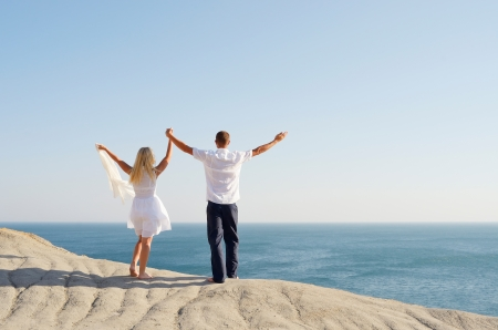 Young couple standing on a rock and raised her hands to the sky photo