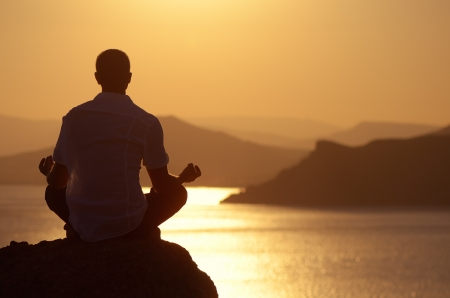 lotus pose: Guy meditating at sunset sitting on a rock by the sea Stock Photo
