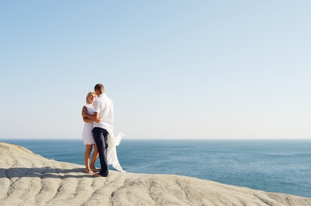 Young couple dressed in white talking, standing on a rock by the sea photo