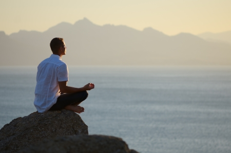 Guy sitting on a rock in the lotus position and looking at the setting sun photo