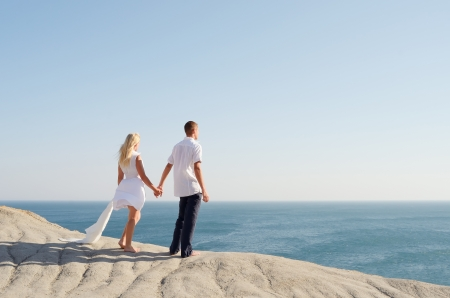 Young couple dressed in white, holding hands and looking at the sea photo