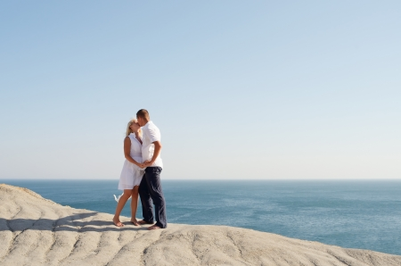 Young couple kissing while standing on a cliff near the sea photo