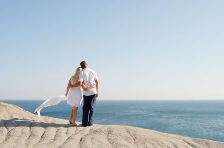 Man and woman standing arm in arm on a rock and watching the sea photo