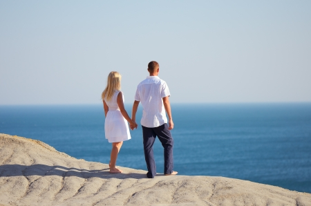 Young couple looking at the sea holding hands photo