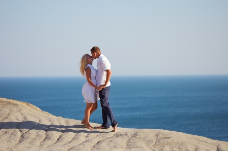 Young couple kissing on a rock by the sea photo