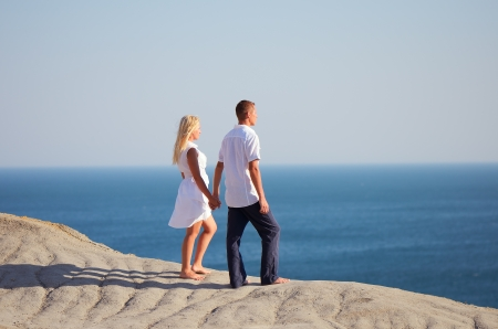 �ouple standing on a mountain and looking at the sea holding hands photo