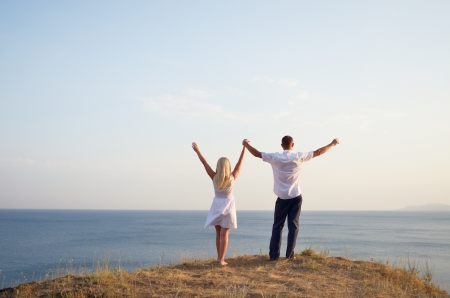 lover boy: Man and woman raising their hands to the sky while standing on the beach Stock Photo