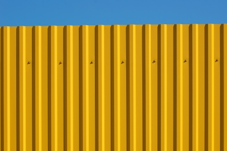 A fragment of a fence with a yellow sheeting photo