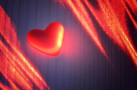 Sign of love from the polymer in the light of the laser on a wooden board Stock Photo - 17046008