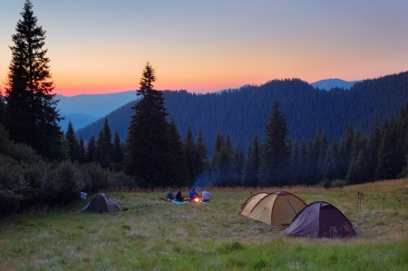 Evening by the fire in the mountains  Camping in tents in the mountains  photo
