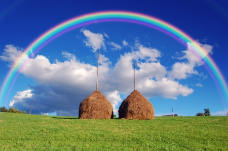 backwoods: Summer mountain village landscape with a rainbow over haystacks