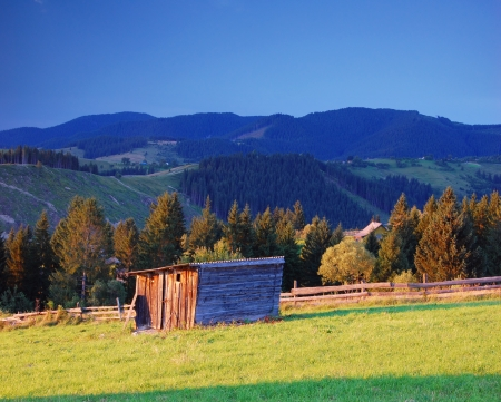 Evening landscape in mountains with wooden barn