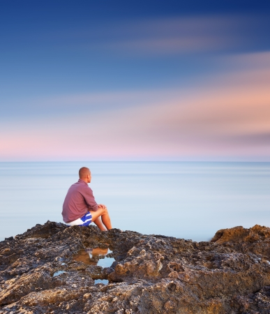 Evening landscape  A man sitting on a rock by the sea photo