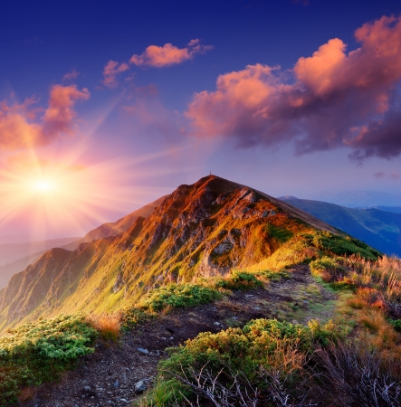 Beautiful summer sunrise in mountains  Path along the ridge leading to summit
