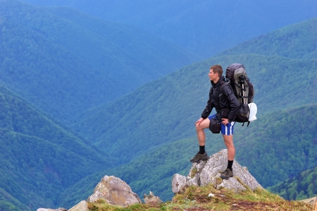 Fellow traveler with a backpack standing on a rock in the mountains photo