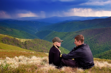 Loving couple in the mountains  Stormy sky photo