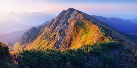 Rising sun lights up a mountain ridge photo