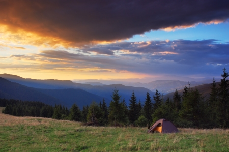 Evening landscape with beautiful sky and tourist tent in the mountains