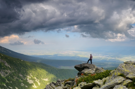 Man standing on a rock in the mountains and looks into the distance photo