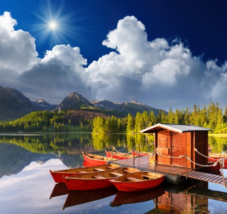 Beautiful red boat in a mountain lake Strbske Pleso, Slovakia, Europe photo