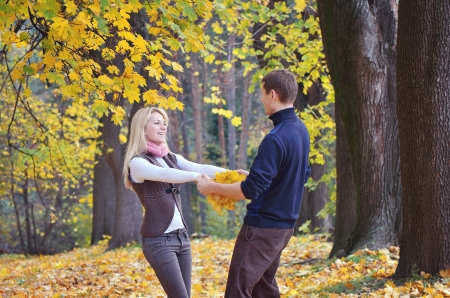 Loving couple in the autumn forest with yellow leaves photo