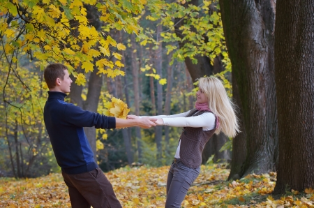 Happy couple in the autumn park circling hand in hand photo