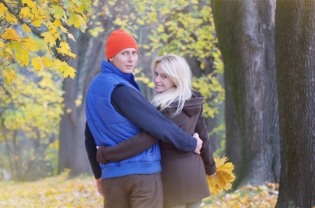 Young loving couple walking arm in arm in the autumn park photo