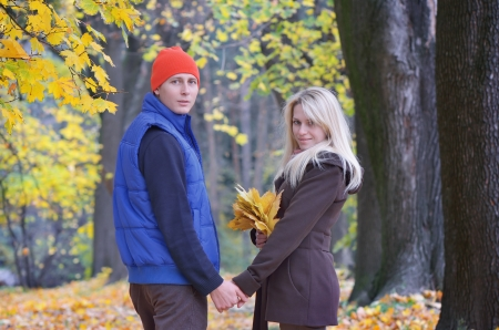Lovers male and female walking in the autumn park photo