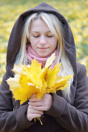 admires: Happy woman admires her bouquet of autumn leaves