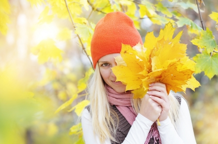Beautiful young blonde woman flirting with yellow autumn leaves. photo