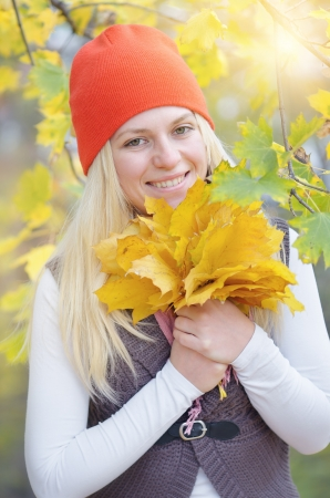 Happy young blond woman smiling and holding a bouquet of yellow autumn leaves Archivio Fotografico