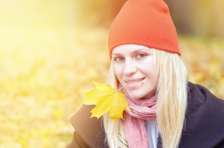 Blonde girl in orange hat holding autumn leaf in his mouth photo
