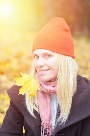 Blonde woman in orange hat with yellow autumn leaf photo